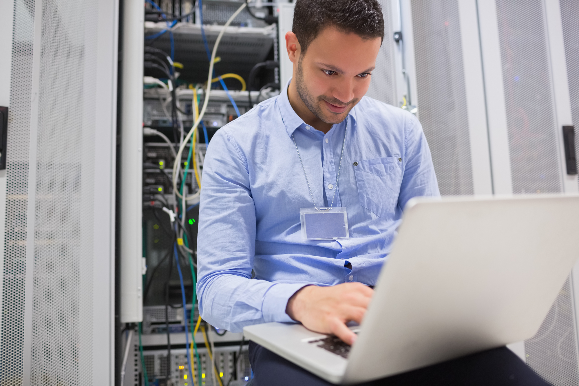 Man using laptop to check servers in data center